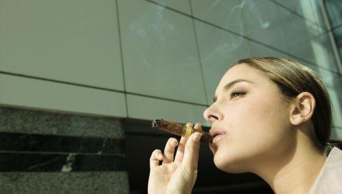 Eine Frau raucht eine Zigarre.