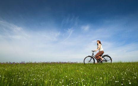 Das Bild zeigt eine Frau, die mit einem Rad über eine Wiese fährt.