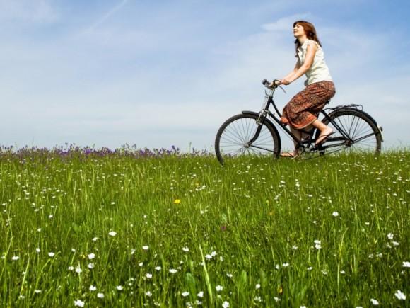 Burnout-Syndrom: Das Bild zeigt eine Frau, die mit einem Rad über eine Wiese fährt.