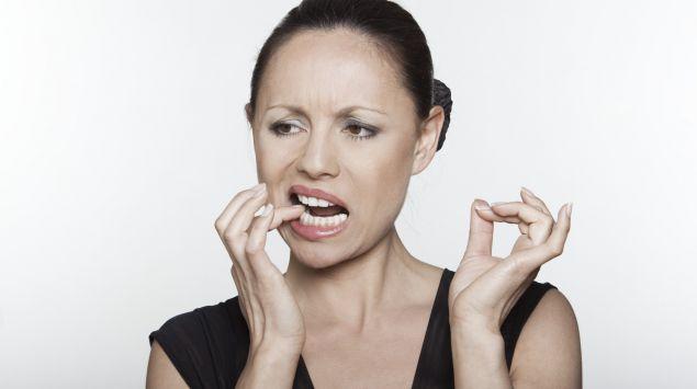 Das Bild zeigt eine Frau, die sich an den Zahn greift.