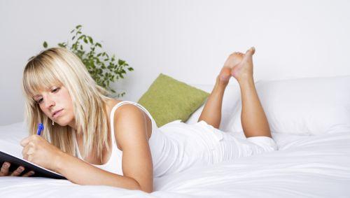 Das Bild zeigt eine junge Frau, die auf dem Bett liegt und etwas in ein Buch schreibt.