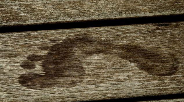 Nasser Fußabdruck auf einer Holzdiele