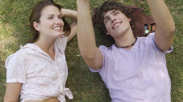 Ein Paar liegt auf einer Wiese und betrachtet einen Fußball.