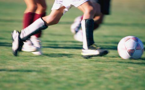 Das Bild zeigt einen Fußballer, der mit dem Ball am Fuß über den Platz rennt.