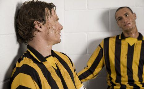 Das Bild zeigt zwei verdreckte Fußballspieler.