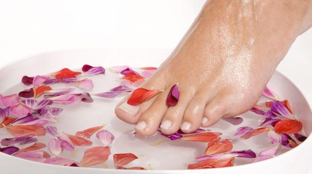 Das Bild zeigt einen Fuß, der in ein Blumenbad entaucht.