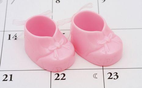 Ein Kalender, darauf ein Paar rosa Babyschuhe.