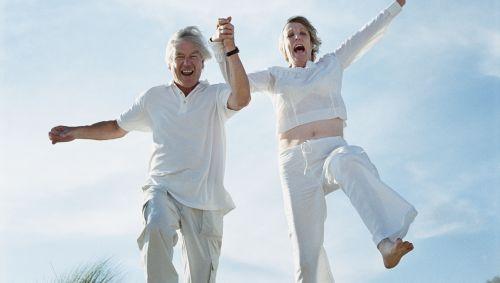 Ein älteres Paar hält sich an den Händen und springt vergnügt am Strand.