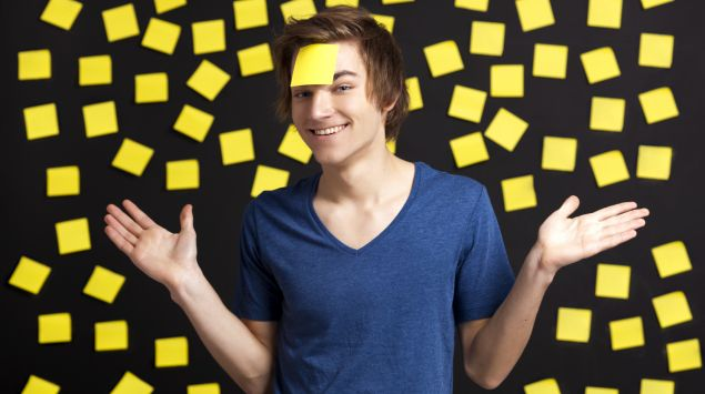 Das Bild zeigt einen jungen Mann vor einer Wand mit Post-its, von denen eines auf seiner Stirn klebt.