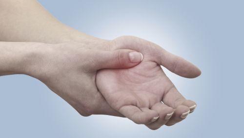 Eine Person hält sich sich die schmerzende Hand.