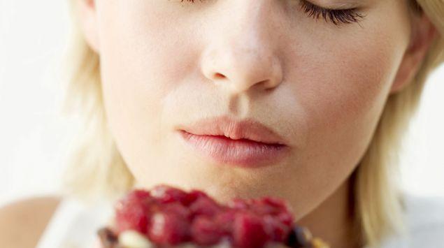Man sieht eine Frau, die mit geschlossenen Augen in ein Obsttörtchen beißt.