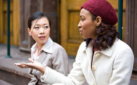 Zwei Frauen unterhalten sich auf einer Bank.
