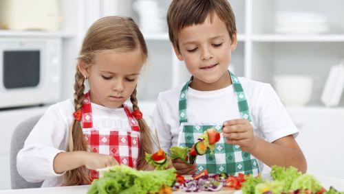 Das Bild zeigt Kinder die Gemüsespieße zubereiten.