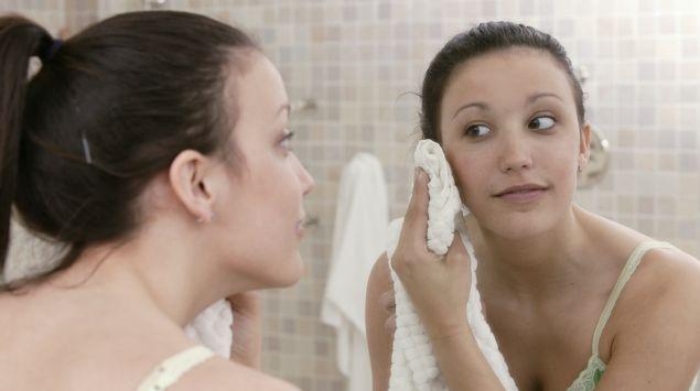 Eine Frau trocknet sich das Gesicht ab während sie in den Spiegel schaut.