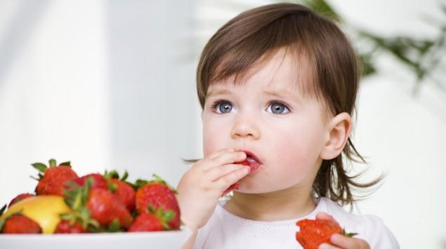 Das Bild zeigt ein kleines Mädchen, das Erdbeeren isst.