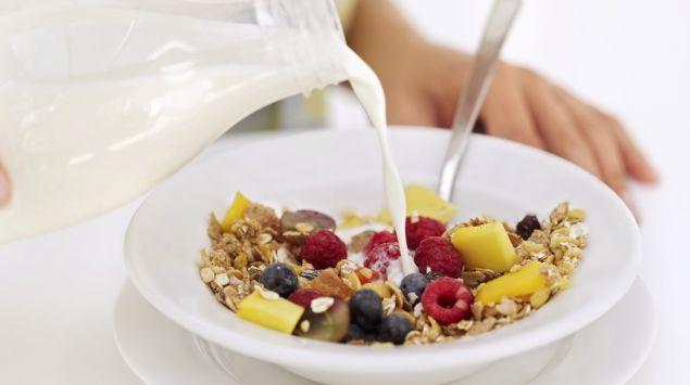 Das Bild zeigt einen Teller mit Müsli in den Milch gegossen wird.