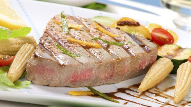 Das Bild zeigt einen Teller mit gebratenem Fisch und Gemüse.