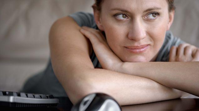 Eine Frau hat den Kopf auf ihre Armen auf dem Tisch abgelegt und blickt grübelnd zur Seite.