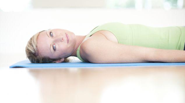 Eine Frau liegt entspannt auf einer Gymnastikmatte.