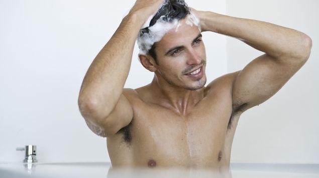Man sieht einen jungen Mann, der sich die Haare wäscht.