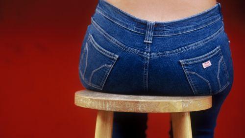 Das Bild zeigt eine Frau, die auf einem Hocker sitzt.