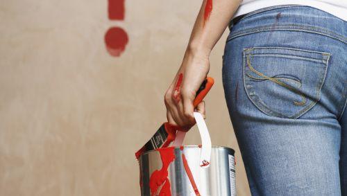 Die Rückansicht einer Frau mit einem Eimer roter Farbe und einem Pinsel, im Hintergrund ein Fragezeichen an der Wand.