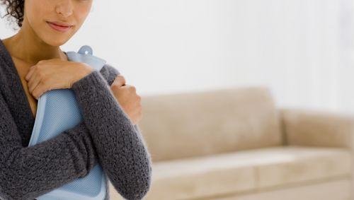 Das Bild zeigt eine Frau mit einer Wärmflasche in ihren Armen.