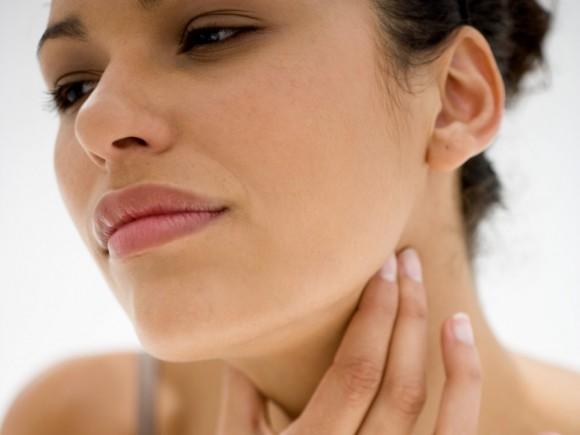 Pfeiffersches Drüsenfieber: Das Bild zeigt eine Frau, die sich an den unbedeckten Hals greift.