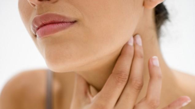 Das Bild zeigt eine Frau, die sich an den unbedeckten Hals greift.