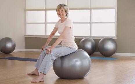 Rückenschmerzen: EIne ältere Frau sitzt aufrecht auf einem Gymnastikball.