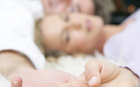 Ein Paar liegt auf dem Bett, ihre Hände berühren sich.