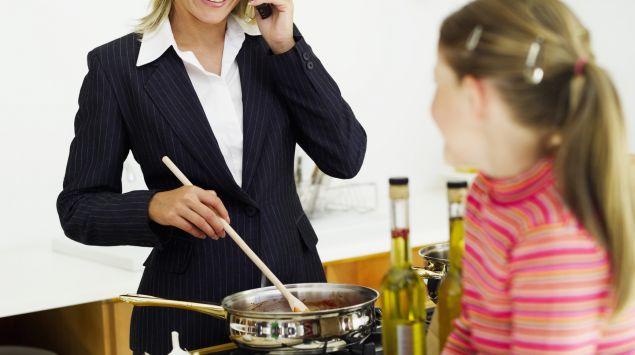 Das Bild zeigt eine Geschäftsfrau mit Handy am Ohr beim Kochen und ein Mädchen.
