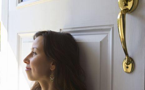 Eine junge Frau sitzt vor ihrer Haustür.