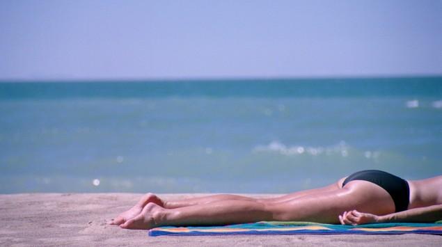 Das Bild zeigt die Beine einer Frau, die sich am Strand sonnt.