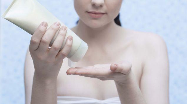 Eine Frau benutzt eine Cremetube.