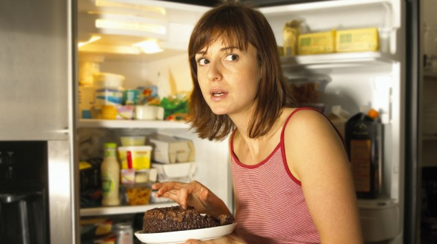 Eine Frau vor dem geöffneten Kühlschrank, sie hält einen Teller mit Schokoladenkuchen in der Hand.