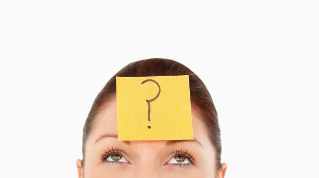Eine Frau mit einem Post-It auf der Stirn, auf dem ein Fragezeichen steht.