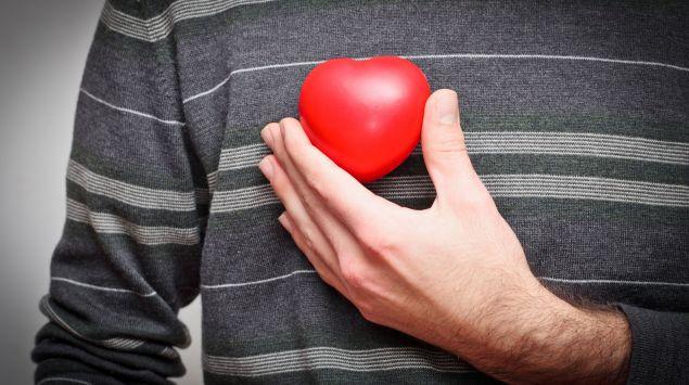 Ein Mann hält ein Herz an seine rechte Brust.