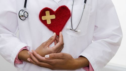 Das Bild zeigt eine Ärztin, die ein gestricktes Herz in den Händen hält.