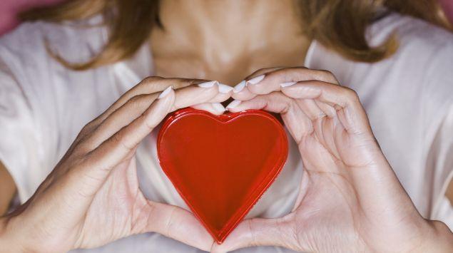 Das Bild zeigt eine Frau, die ein Herz in der Hand hält.