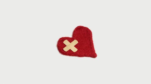 Man sieht ein rotes Herz aus Filz mit einem Pflasterkreuz darauf.