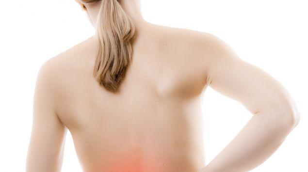 Das Bild zeigt eine Frau, die sich an den Rücken greift.