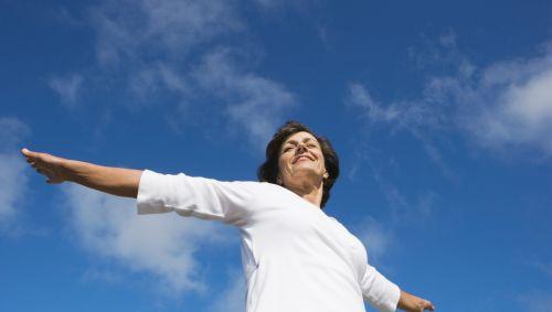 Eine glücklich aussehende Frau unter freiem Himmel.