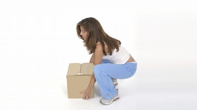 Ein Frau hebt einen Karton aus der Hocke.