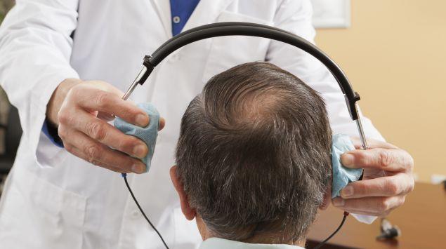 Ein Ohrenarzt setzt einem Mann Kopfhörer für einen Hörtest auf.