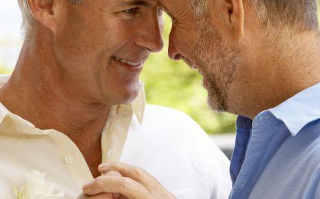 Ein homosexuelles, männliches Paar, an einer Hand ist ein Ehering zu sehen.
