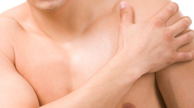 Das Bild zeigt einen Mann mit freiem Oberkörper, der sich die Schulter hält.