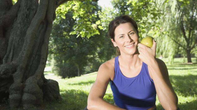 Das Bild zeigt eine Frau, die einen Apfel in der Hand hat.