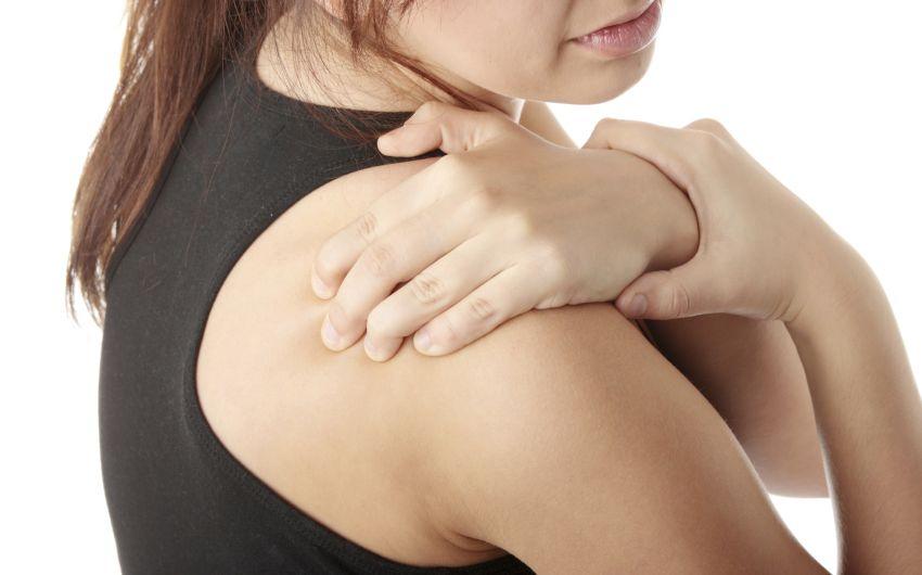 Das Bild zeigt eine Frau, die sich an die Schulter fasst.