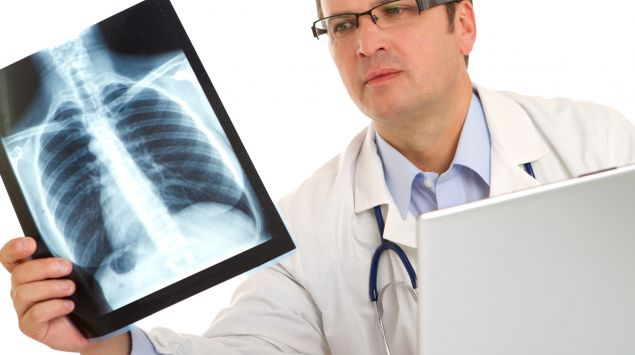 Das Bild zeigt einen Arzt mit Röntgenbild.